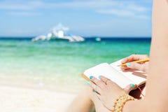 Η Ευρωπαία γυναίκα κάθεται στην ακτή της τροπικής τυρκουάζ θάλασσας και από τη μάνδρα στο σημειωματάριο στην ηλιόλουστη θερινή ημ Στοκ φωτογραφίες με δικαίωμα ελεύθερης χρήσης