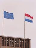 Η Ευρωπαϊκή Ένωση και οι ολλανδικές σημαίες σε ένα κτήριο μια θλιβερή ημέρα Στοκ φωτογραφία με δικαίωμα ελεύθερης χρήσης