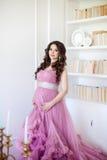 Η ευτυχής έγκυος γυναίκα στο ρόδινο φόρεμα στέκεται κοντά στα ράφια των βιβλίων Στοκ Εικόνες