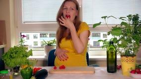 Η ευτυχής έγκυος γυναίκα συζύγων τρώει τα κόκκινα μούρα και εξετάζει τη κάμερα με το χαμόγελο στο πρόσωπο φιλμ μικρού μήκους