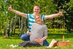 Η ευτυχής έγκυος παρουσίαση ζευγών φυλλομετρεί επάνω Στοκ φωτογραφία με δικαίωμα ελεύθερης χρήσης