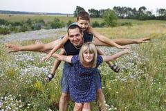 Η ευτυχής αγαπώντας οικογένεια περνά ένα Σαββατοκύριακο στη φύση στοκ εικόνες