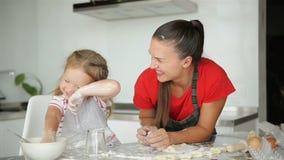 Η ευτυχής αγαπώντας οικογένεια προετοιμάζει το αρτοποιείο από κοινού Το κορίτσι κορών μητέρων και παιδιών μαγειρεύει τα μπισκότα  απόθεμα βίντεο