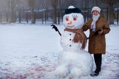 Η ευτυχής ανώτερη γυναίκα sculpt και αγκαλιάζει έναν μεγάλο πραγματικό χιονάνθρωπο Στοκ εικόνα με δικαίωμα ελεύθερης χρήσης