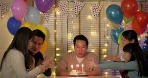 Η ευτυχής ασιατική αρσενική συνεδρίαση στον πίνακα γιορτάζει τα γενέθλιά του με ένα κέικ φιλμ μικρού μήκους