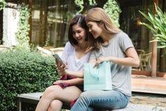 Η ευτυχής ασιατική γυναίκα φίλων με το smartphone προσέχει τα πολυμέσα στο κινητό τηλέφωνο στον καφέ στοκ φωτογραφία με δικαίωμα ελεύθερης χρήσης