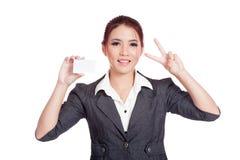 Η ευτυχής ασιατική επιχειρηματίας παρουσιάζει το σημάδι νίκης και BL Στοκ Εικόνες