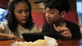 Η ευτυχής ασιατική προσοχή παιδιών στο κινητό τηλέφωνο και απολαμβάνει τις πυρκαγιές πατατών, σε αργή κίνηση του αδελφού και της  φιλμ μικρού μήκους
