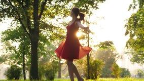 Η ευτυχής γελώντας γυναίκα στο κόκκινο φόρεμα που χορεύει και που γυρίζει γύρω, ήλιος λάμπει μέσω της διαφανούς φούστας απόθεμα βίντεο