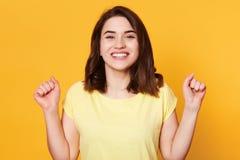 Η ευτυχής γυναίκα έντυσε την περιστασιακή μπλούζα, σφίγγοντας τις πυγμές της με τον ενθουσιασμό, εορτασμός, στόχος επίτευξης, τα  στοκ φωτογραφίες