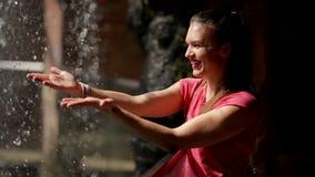 Η ευτυχής γυναίκα απολαμβάνει τις μειωμένες πτώσεις νερού Το νερό είναι η πηγή ζωής φιλμ μικρού μήκους