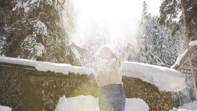Η ευτυχής γυναίκα απολαμβάνει το ηλιόλουστο χειμερινό πρωί, εκτίναξη στον αέρα που περιστρέφει στο χιόνι και που λαμπιρίζει στον  φιλμ μικρού μήκους