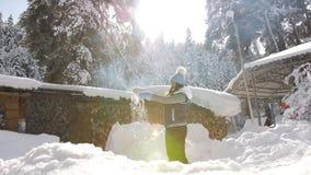 Η ευτυχής γυναίκα απολαμβάνει το ηλιόλουστο χειμερινό πρωί, εκτίναξη στον αέρα που περιστρέφει στο χιόνι και που λαμπιρίζει στον  απόθεμα βίντεο