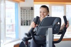 Η ευτυχής γυναίκα είναι δεσμευμένη σε ένα στάσιμο ποδήλατο Στοκ εικόνα με δικαίωμα ελεύθερης χρήσης