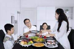 Η ευτυχής γυναίκα εξυπηρετεί τα γεύματα για την οικογένειά της στοκ εικόνες