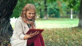Η ευτυχής γυναίκα εφήβων χαλαρώνει στο πάρκο φθινοπώρου Κίτρινα δέντρα, όμορφος χρόνος πτώσης απόθεμα βίντεο