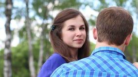Η ευτυχής γυναίκα και ο νεαρός άνδρας κάθονται στον πάγκο και τη γυναίκα απόθεμα βίντεο
