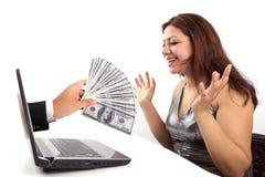 Η ευτυχής γυναίκα κερδίζει τα σε απευθείας σύνδεση χρήματα Στοκ Φωτογραφία