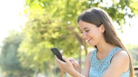 Η ευτυχής γυναίκα κοιτάζει βιαστικά την περιεκτικότητα σε smartphone σε ένα πάρκο απόθεμα βίντεο