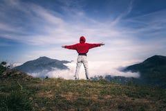 Η ευτυχής γυναίκα με τις ανοικτές αγκάλες μένει στην αιχμή της άκρης απότομων βράχων βουνών κάτω από τον ελαφρύ ουρανό απολαμβάνο στοκ εικόνες