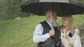 Η ευτυχής γυναίκα με τον ανώτερο άνδρα περπατά κατά τη διάρκεια της βροχής στο πάρκο, γάμος από prexy φιλμ μικρού μήκους