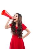 Η ευτυχής γυναίκα με το κόκκινο φόρεμα και φωνάζει με megaphone στοκ φωτογραφία