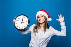 Η ευτυχής γυναίκα με το ρολόι παρουσιάζει το νέο κόμμα έτους ότι 12 η ώρα αρχίζει στο μπλε υπόβαθρο Στοκ φωτογραφία με δικαίωμα ελεύθερης χρήσης