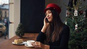 Η ευτυχής γυναίκα μιλά στην τηλεφωνική συνεδρίαση σε έναν άνετο καφέ στην κρύα χειμερινή ημέρα φιλμ μικρού μήκους
