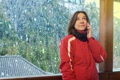Η ευτυχής γυναίκα μιλά στο τηλέφωνο το χειμώνα στοκ εικόνα