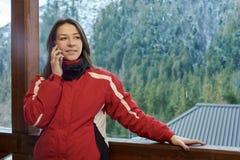 Η ευτυχής γυναίκα μιλά στο τηλέφωνο το χειμώνα στοκ φωτογραφίες