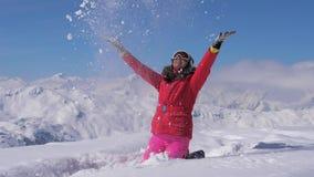 Η ευτυχής γυναίκα παίζει στο χιόνι του βουνού μια ηλιόλουστη ημέρα, σε αργή κίνηση, hd φιλμ μικρού μήκους