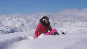 Η ευτυχής γυναίκα παίζει στο χιόνι του βουνού μια ηλιόλουστη ημέρα, σε αργή κίνηση, hd απόθεμα βίντεο