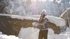Η ευτυχής γυναίκα πλέκει μέσα το πουλόβερ και το καπέλο γουνών απολαμβάνει ένα ηλιόλουστο παγωμένο πρωί, ρίχνει το χιόνι και περι φιλμ μικρού μήκους