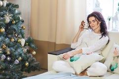 Η ευτυχής γυναίκα πλεκτή στη λευκό φθορά χαλαρώνει στο σπίτι για τα Χριστούγεννα στοκ εικόνα με δικαίωμα ελεύθερης χρήσης