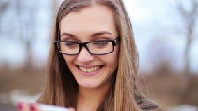 Η ευτυχής γυναίκα που χρησιμοποιεί ένα έξυπνο τηλέφωνο στην οδό με το υπόβαθρο απόθεμα βίντεο