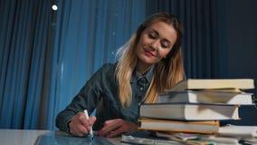 Η ευτυχής γυναίκα σπουδαστής σε ένα πουκάμισο τζιν, γράφει σε έναν μικρό πίνακα Κινηματογράφηση σε πρώτο πλάνο απόθεμα βίντεο