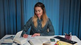 Η ευτυχής γυναίκα σπουδαστής σε ένα πουκάμισο τζιν, γράφει σε ένα εγχειρίδιο Κατόπιν γυρίζει στη κάμερα και χαμογελά Πορτρέτο απόθεμα βίντεο