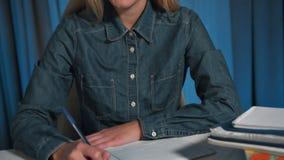 Η ευτυχής γυναίκα σπουδαστής σε ένα πουκάμισο τζιν, γράφει σε ένα εγχειρίδιο Λύνει τα επιχειρησιακά προβλήματα ακολουθώντας κινημ φιλμ μικρού μήκους