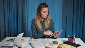 Η ευτυχής γυναίκα σπουδαστής σε ένα πουκάμισο τζιν, χρησιμοποιεί μια ταμπλέτα Κατόπιν γυρίζει στη κάμερα και χαμογελά Πορτρέτο απόθεμα βίντεο