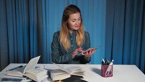 Η ευτυχής γυναίκα σπουδαστής σε ένα πουκάμισο τζιν, χρησιμοποιεί μια ταμπλέτα Κατόπιν γυρίζει στη κάμερα και τον αντίχειρα επάνω απόθεμα βίντεο