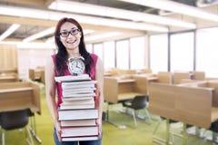 Η ευτυχής γυναίκα σπουδαστής φέρνει το σωρό των βιβλίων και του ρολογιού στοκ φωτογραφίες