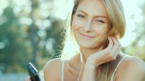 Η ευτυχής γυναίκα στα ακουστικά ακούει τη μουσική, χρησιμοποιεί ένα smartphone Ο ήλιος φωτίζει υπέροχα την τρίχα της φιλμ μικρού μήκους