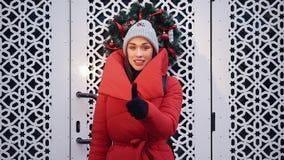 Η ευτυχής γυναίκα στα κόκκινα σακάκια περιμένει πριν από τις άσπρες πύλες έξω απόθεμα βίντεο