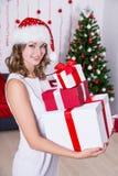 Η ευτυχής γυναίκα στο καπέλο santa με παρουσιάζει κοντά στο χριστουγεννιάτικο δέντρο Στοκ εικόνες με δικαίωμα ελεύθερης χρήσης