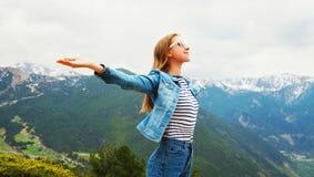 Η ευτυχής γυναίκα ταξιδιού απολαμβάνει τα βουνά καθαρού αέρα αυξάνει τα χέρια επάνω στοκ εικόνες με δικαίωμα ελεύθερης χρήσης