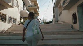 Η ευτυχής γυναίκα τουριστών ταξιδιού αναρριχείται στα σκαλοπάτια στο Άγιο Νικόλαο, Κρήτη, Ελλάδα απόθεμα βίντεο