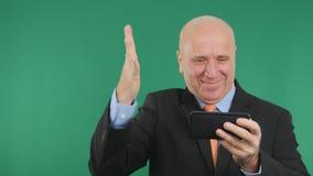 Η ευτυχής εικόνα επιχειρηματιών διάβασε στο τηλέφωνο κυττάρων τις οικονομικές καλές ειδήσεις και κάνει τη νίκη Han στοκ φωτογραφία με δικαίωμα ελεύθερης χρήσης
