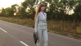 Η ευτυχής επιχειρησιακή γυναίκα στο επιχειρησιακό κοστούμι πηγαίνει στο δρόμο της να εργαστεί με τα σημαντικά έγγραφα στο χαρτοφύ απόθεμα βίντεο
