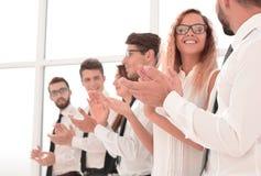 Η ευτυχής επιχειρησιακή ομάδα επιδοκιμάζει στεμένος στο γραφείο στοκ εικόνα με δικαίωμα ελεύθερης χρήσης