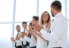 Η ευτυχής επιχειρησιακή ομάδα επιδοκιμάζει στεμένος στο γραφείο στοκ εικόνα